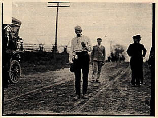 """The Pedestrian"" at age 69, walking along a dirt road near Chicago where he arrived on Nov. 27th, 1907, after a walk of 1200 miles from Portland, Maine. DN-0052117, Chicago Daily News collection, courtesy of the Chicago Historical Society."